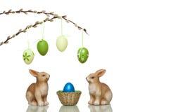 Los conejitos de pascua lindos al lado de Pascua jerarquizan con los huevos Fotografía de archivo