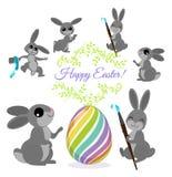 Los conejitos de pascua pintan los huevos ilustración del vector