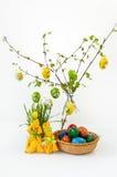 Los conejos amarillos de Pascua colorearon los huevos que colgaban de ramas del abedul con las hojas y la hierba verde Fotos de archivo libres de regalías