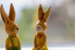 Los conejos de la decoración se colocan cerca de una ventana Imagenes de archivo