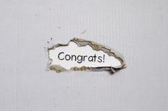 Los congrats de la palabra que aparecen detrás del papel rasgado foto de archivo