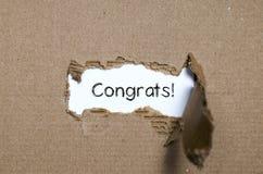Los congrats de la palabra que aparecen detrás del papel rasgado fotografía de archivo