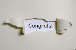 Los congrats de la palabra que aparecen detrás del papel rasgado imagen de archivo libre de regalías