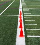 Los conos anaranjados en un césped del verde colocan la línea lateral blanca para el tra de la velocidad Fotografía de archivo