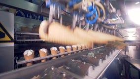 Los conos vacíos de la oblea se están poniendo en una máquina de la fábrica mientras que los conos llenados de crema están consig almacen de video