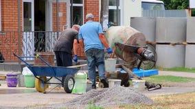 Los constructores están amasando una solución concreta con un mezclador concreto metrajes