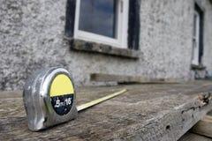 Los constructores miden en el andamio en el solar foto de archivo