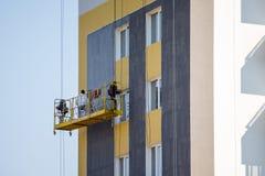 Los constructores pusieron el yeso en las paredes de una estructura moderna de gran altura imagen de archivo libre de regalías