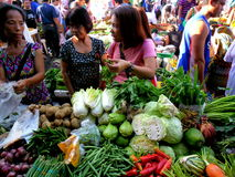 Los consumidores compran a un vendedor vegetal en un mercado en Cainta, Rizal, Filipinas, Asia Fotos de archivo