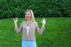 Los controles de la mujer joven en manos de llaves del finger disfrutan y las risas, s Foto de archivo