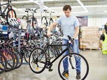 Los controles del hombre montan en bicicleta antes de comprar en tienda de los deportes Fotos de archivo