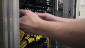 Los controles del ingeniero de las TIC abren el cable de Ethernet del estante y del enchufe del servidor hacia fuera almacen de metraje de vídeo