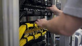 Los controles del ingeniero de las TIC abren el estante del servidor y enchufan el cable metrajes