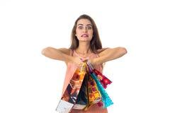 Los controles divertidos jovenes de la muchacha delante mucho de los paquetes se aíslan del fondo blanco Imagen de archivo libre de regalías