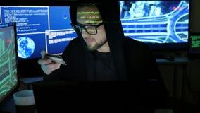 Los controles robados del pirata informático de la tarjeta de banco en las manos, criminal cibernético, roban finanzas a través d metrajes