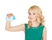Los controles rubios hermosos en una mano cosméticos de una botella Foto de archivo