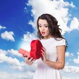 Los controles sorprendidos los jóvenes de la mujer abren la caja del corazón Fotografía de archivo libre de regalías