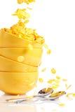 Los copos de maíz de oro caen en los tazones de fuente foto de archivo libre de regalías