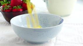 Los copos de maíz se vierten en el cuenco para el desayuno con leche y la fresa almacen de video