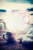 Los copos de nieve asaltan con la bebida caliente, las manoplas que hacen punto y el bokeh en travesaño de la ventana de la helad fotografía de archivo