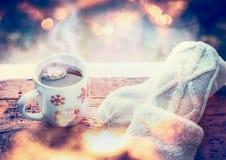 Los copos de nieve asaltan con la bebida y las manoplas calientes en travesaño de la ventana con el bokeh imagenes de archivo