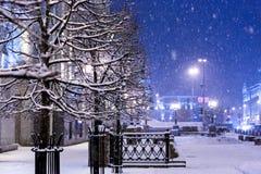 Los copos de nieve caen abajo en la ciudad de la noche, cubriendo árboles, los faroles Fotografía de archivo libre de regalías