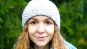 Los copos de nieve caen en el sombrero y el pelo rubio de la muchacha contra árbol de la piel almacen de metraje de vídeo