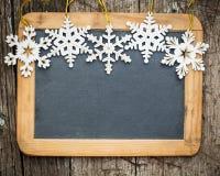 Los copos de nieve confinan con el espacio en blanco de madera de la pizarra Imagen de archivo