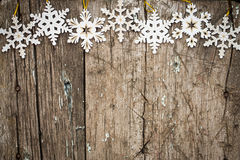 Los copos de nieve confinan con la madera Imagenes de archivo