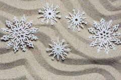 Los copos de nieve decorativos de la Navidad mienten en la arena de la playa imagenes de archivo