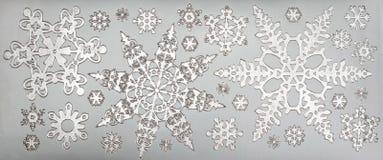 Los copos de nieve de plata se cierran encima de follaje del metal Foto de archivo libre de regalías