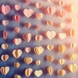 Los corazones coloridos empapelan la ejecución de la guirnalda en la pared Fondo romántico del día de tarjeta del día de San Vale Foto de archivo