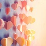 Los corazones coloridos empapelan la ejecución de la guirnalda en la pared Fondo romántico del día de tarjeta del día de San Vale Imagen de archivo