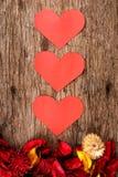 Los corazones con popurrí rojo florecen los pétalos en el fondo de madera - serie 3 Imagen de archivo libre de regalías