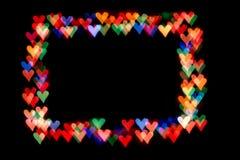 Los corazones de Bokeh aislados en los corazones negros de un fondo de diversos colores forman el marco foto de archivo libre de regalías