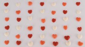 Los corazones de diversos colores se alinearon en el fondo blanco Fotos de archivo