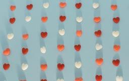 Los corazones de diversos colores se alinearon en fondo azul Imagen de archivo