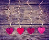 Los corazones de la tarjeta del día de San Valentín del amor de la tela del fieltro que cuelgan en la madera de deriva rústica Fotografía de archivo libre de regalías