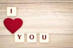 Los corazones de la tarjeta del día de San Valentín en un fondo y un tex de madera te quiero Fotografía de archivo libre de regalías