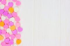 Los corazones del caramelo del día de tarjetas del día de San Valentín echan a un lado frontera sobre la madera blanca foto de archivo