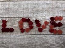 Los corazones del caramelo deletrean AMOR en fondo gris del tablero fotos de archivo