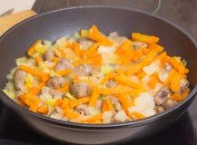 Los corazones del pollo frito con las verduras, zanahorias, cebolla, verdes en un sartén negro, cerraron la cubierta de cristal F Fotos de archivo libres de regalías
