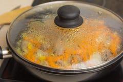 Los corazones del pollo frito con las verduras, zanahorias, cebolla, verdes en un sartén negro, cerraron la cubierta de cristal F Fotografía de archivo libre de regalías