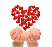 Los corazones en corazón forman volar sobre las manos ahuecadas de la mujer joven, tarjeta de cumpleaños, el día de tarjeta del d Foto de archivo libre de regalías