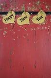 Los corazones haning de la Feliz Año Nuevo en rojo apenaron la madera Foto de archivo libre de regalías