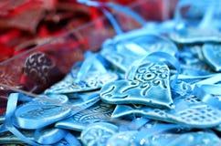 Los corazones hechos a mano azules y rojos de la arcilla para la venta en una Navidad comercializan la feria Imagen de archivo