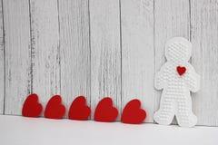Los corazones rojos de la cartulina se arreglan en fila en un fondo de madera blanco Figura plástica de un hombre con un corazón  fotografía de archivo libre de regalías