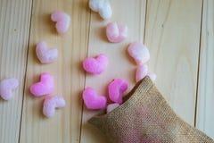 Los corazones rosados desbordan el saco en fondo de madera Imagen de archivo libre de regalías