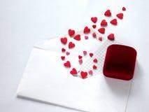 Los corazones vuelan del sobre y la caja para el anillo miente al lado de él Imágenes de archivo libres de regalías