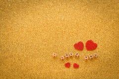 Los corazones y las letras decorativos ocasionales, te amo en un fondo de oro brillante con un lugar se fueron para la inscripció Imagen de archivo libre de regalías